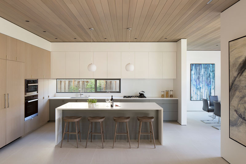 This modern kitchen is connected to the living room and dining room by a floating cedar ceiling. #KitchenDesign #WoodCeiling