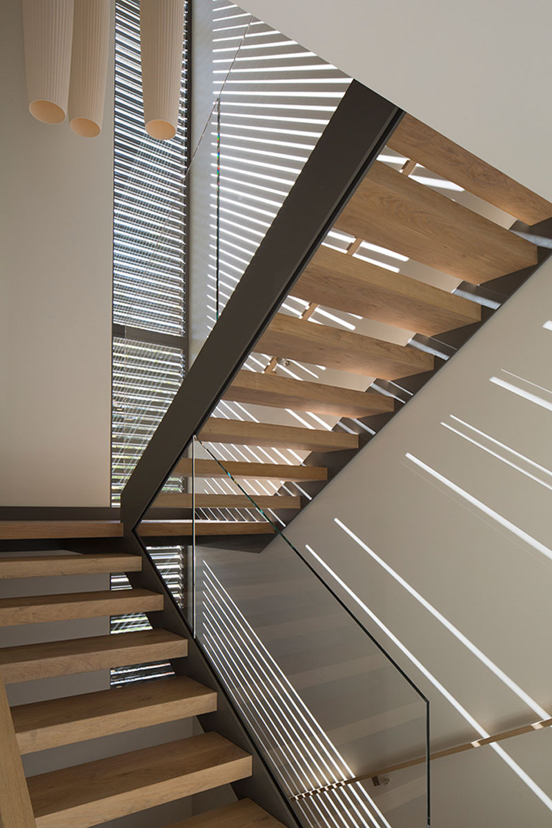 This slender screen runs the height of the front stairwell, that casts rays of sunlight inside during the day. #Stairs #Screen #ModernStairs