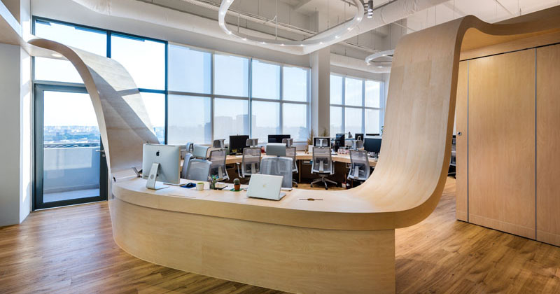 A ribbon-like wood table winds its way throughout this office, and the reason why is meaningful