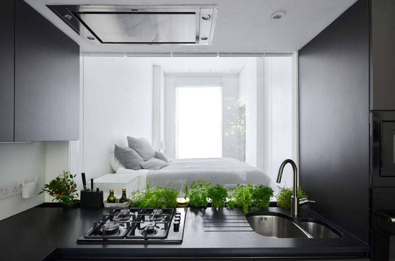 Here's something we don't see too often (if ever). In the kitchen, they have included a glass window backsplash behind the sink, that provides a view through to the bedroom.