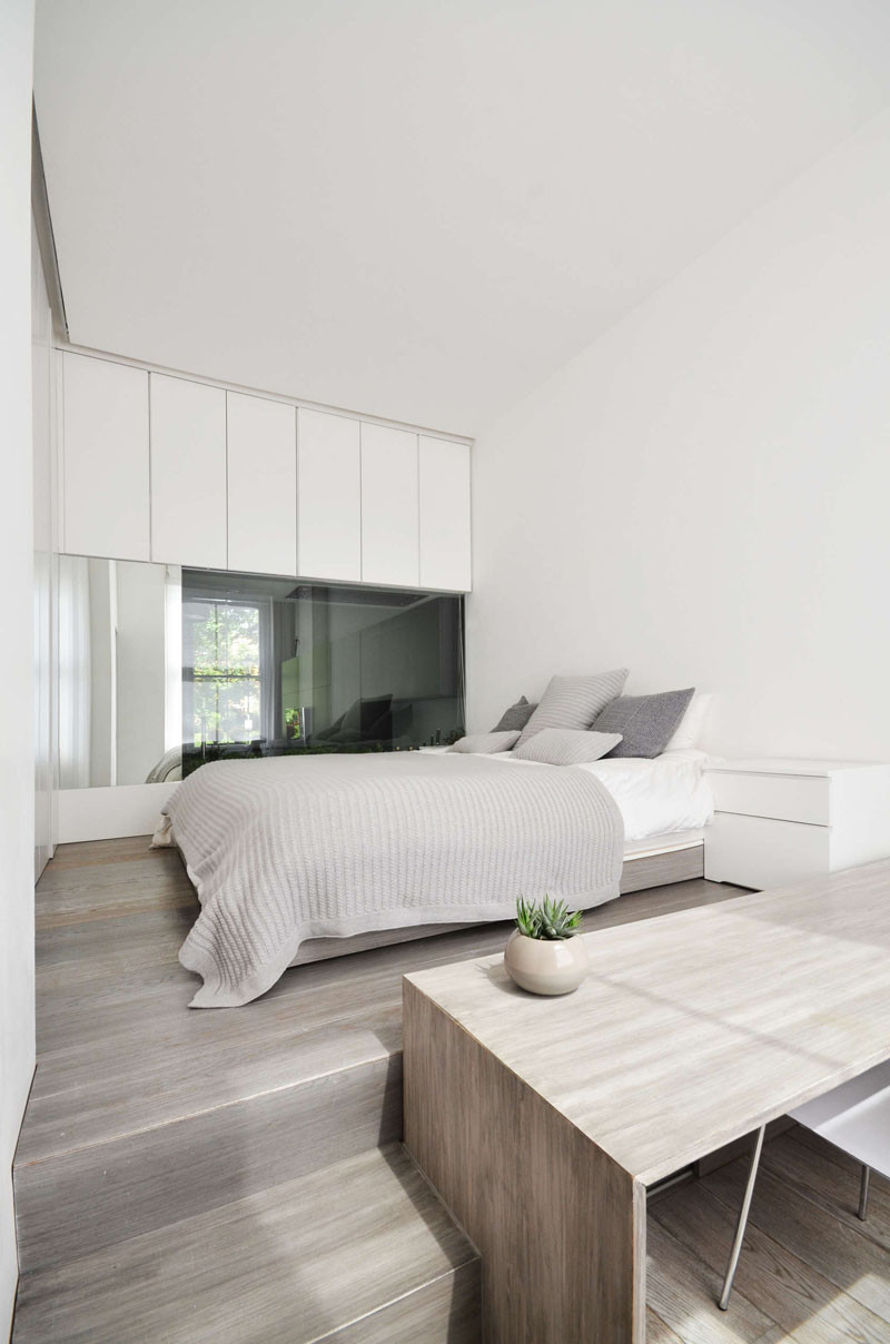 The bed in this bedroom has been raised up to provide a separation from the desk area below
