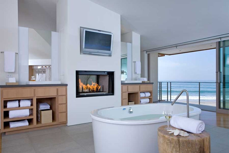 This bathroom has a fireplace and a television included in the design.