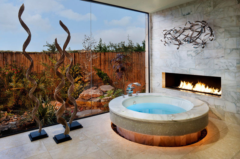 This circular bathtub has a fireplace right next to it for ultimate relaxation.