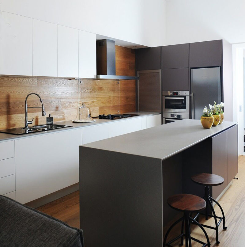 Wood is an excellent backsplash option for those who are trying to be environmentally friendly but don't want to compromise style or function. Once it's been sealed, wood is durable, unique, and adds a warm touch to the kitchen. #WoodBacksplash #KitchenBacksplash #KitchenDesign #BacksplashIDeas