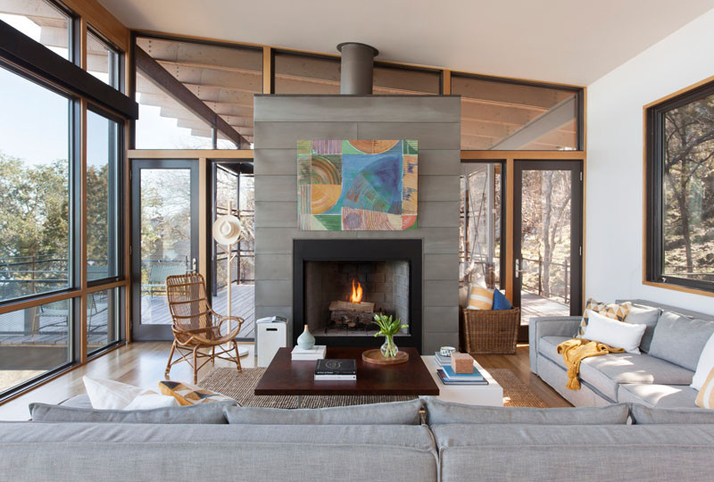 This living room has its furniture focused on the water views and the fireplace. // Blue Lake Retreat by Lake|Flato Architects