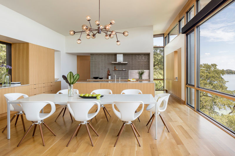 This 8-seater dining table is a pop of white against the surrounding wood floors and cabinetry. The sculptural pendant light above the dining table adds an artistic touch to the space. // Blue Lake Retreat by Lake|Flato Architects