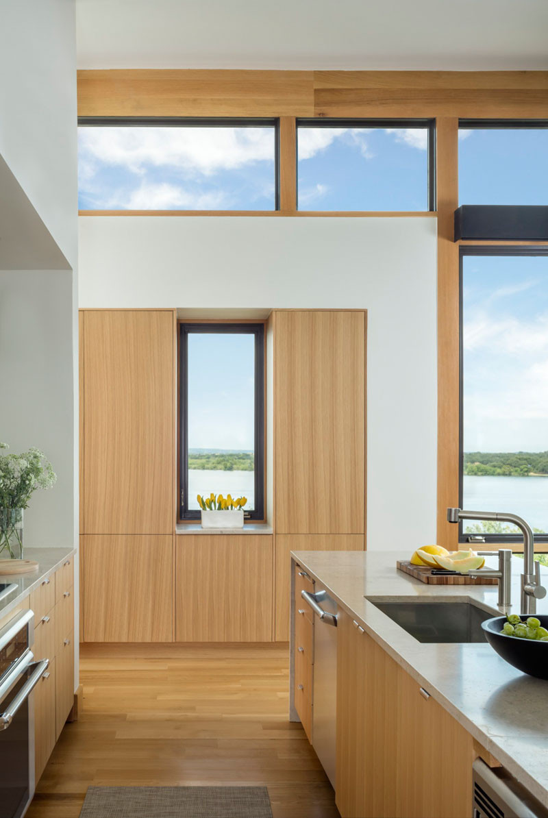 This light wood kitchen has stainless steel appliances and views of the water. // Blue Lake Retreat by Lake|Flato Architects