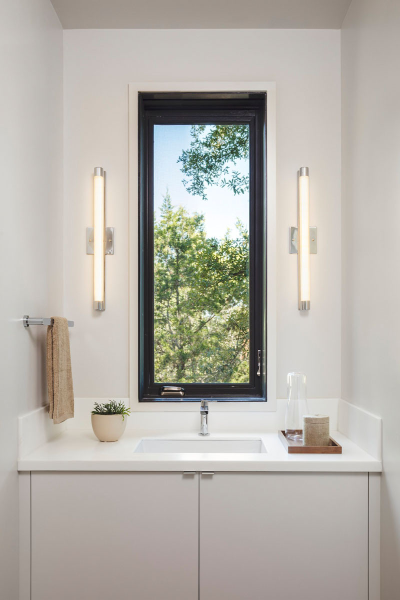 In this bathroom, there is a mirror that slides out to cover the window, otherwise it just has a picturesque view of the trees outside. // Blue Lake Retreat by Lake|Flato Architects