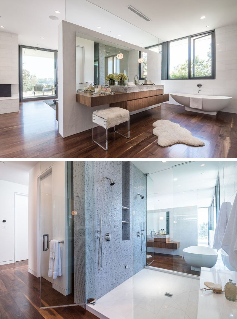 This master bathroom with dual showers and standalone bathtub, is tucked away behind a partition wall behind the bed.