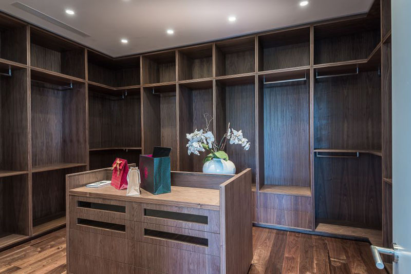 This walk-in closet has plenty of room to hang your clothes, and an island with drawers for additional clothing storage.