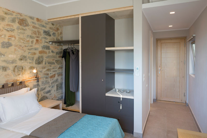 This bedroom in a Greek villa has a partially exposed wardrobe.