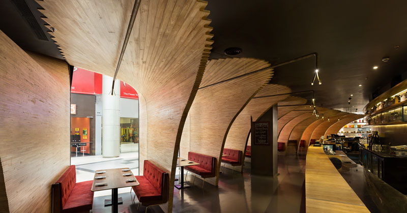 Sculptural wood elements flow from the exterior to the interior of this restaurant