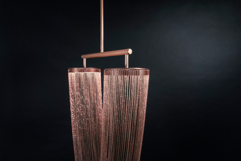 These sculptural lights are made from delicate copper plated chains that hang from two circular forms to create a unique curved shape, all of which is illuminated by a ring of LED lights. #Lighting #SculpturalLighting #LightingDesign #Chandelier #CopperLighting