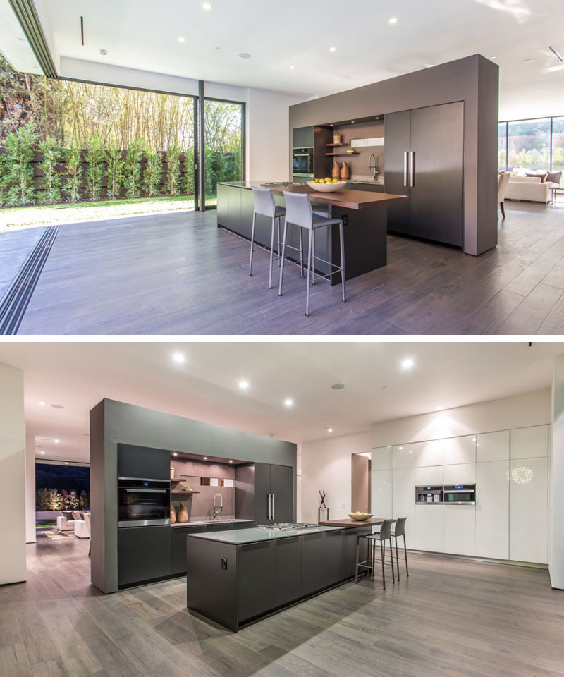 A partial wall separates the kitchen from the dining and living area. It also has an island with a cantilevered wooden counter, making room for bar stools.