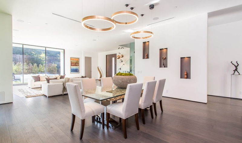 This dining area and living area share the same space, however sculptural lighting helps to define the location of the dining area.
