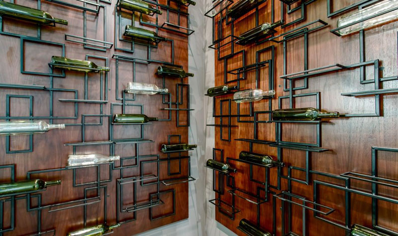 This wine cellar has artistically designed metal bottle shelves.