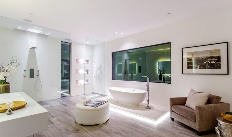 This master bathroom has a floor to ceiling glass partition for the shower, and the bathtub has been raised on a platform surrounded by hidden lighten.