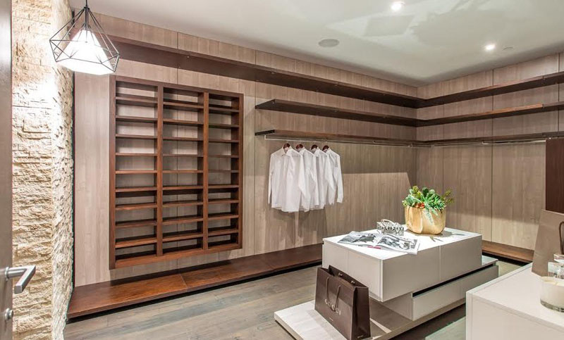 This walk-in closet has plenty of wooden cabinetry and shelves, as well as a central island for storing your accessories.