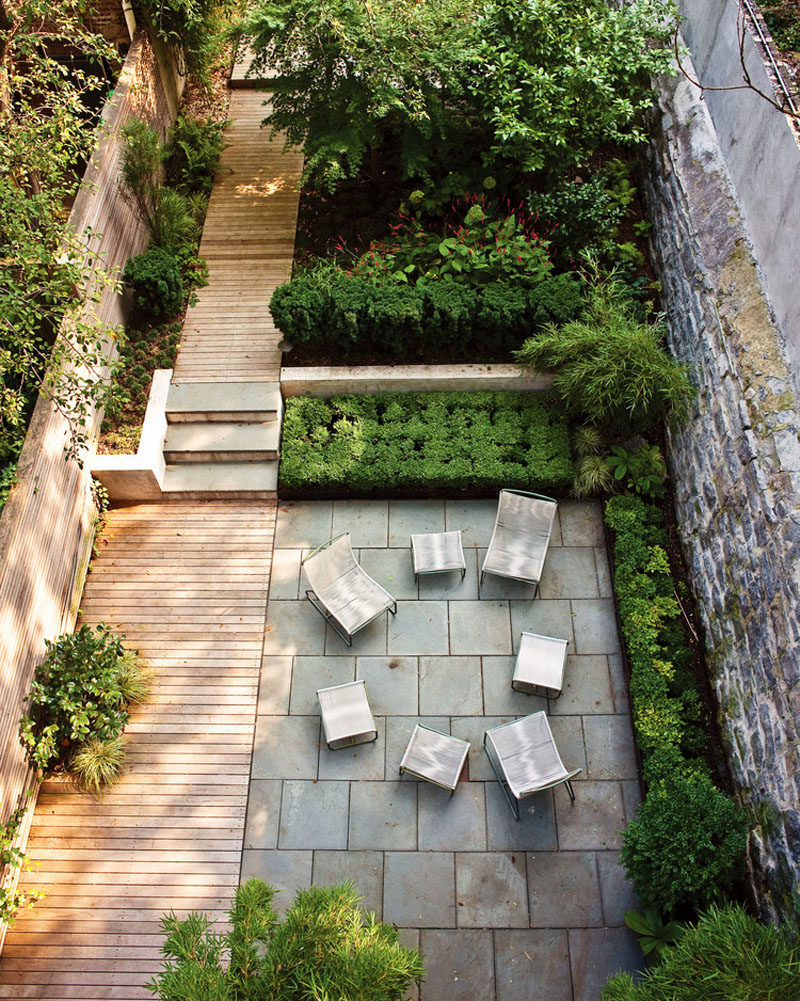 16 Inspirational Backyard Landscape Designs As Seen From Above // A simple, long backyard with a spot to sit together and a garden further back, is connected by a wood plank walkway.