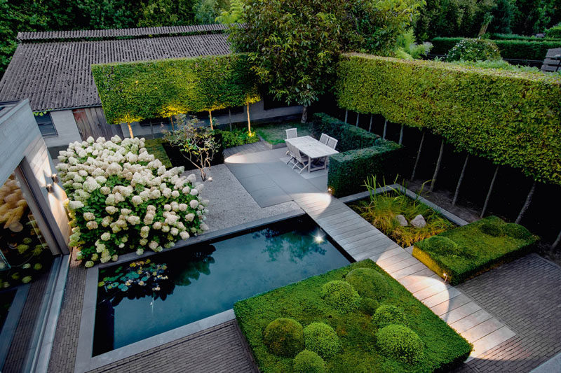 16 Inspirational Backyard Landscape Designs As Seen From Above // This backyard features a natural pool, shaped greenery, a dining space, and an area perfect for sunbathing.