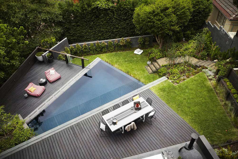 16 Inspirational Backyard Landscape Designs As Seen From Above // This tiered backyard has different levels, a pool level and a dining area separated by a glass wall, this would be the perfect place for a family gathering.