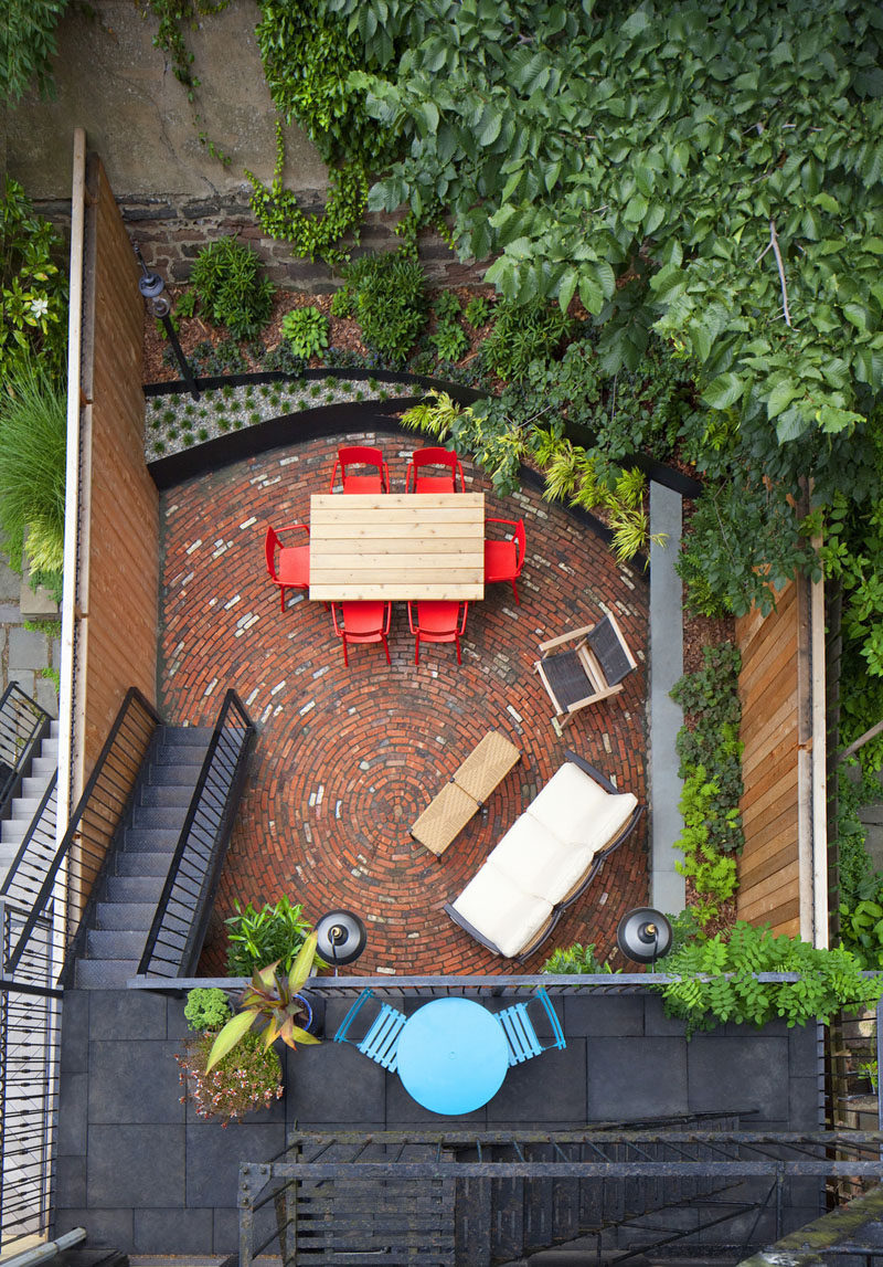 16 Inspirational Backyard Landscape Designs As Seen From Above // The bright colors of the furniture and the circular brick pattern on this back patio in New York, mix with the surrounding greenery and make for a fun space.