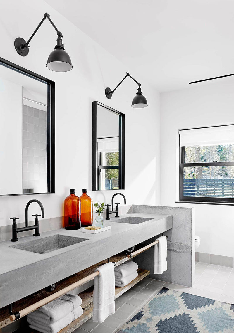 15 Examples of Bathroom Vanities That Have Open Shelving // The custom made concrete vanity in this master bathroom, has dual sinks, a towel railing and open shelving.