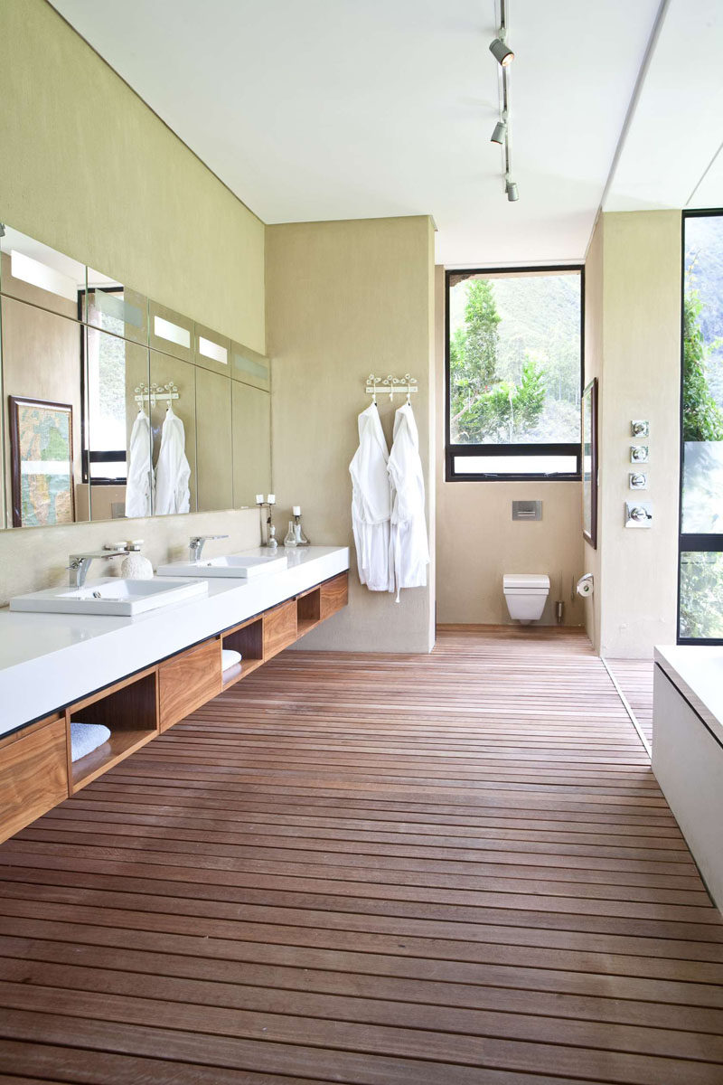 15 Examples of Bathroom Vanities That Have Open Shelving // This spa style bathroom has wood shelves built into the vanity, in keeping with the natural feel of the rest of the space.