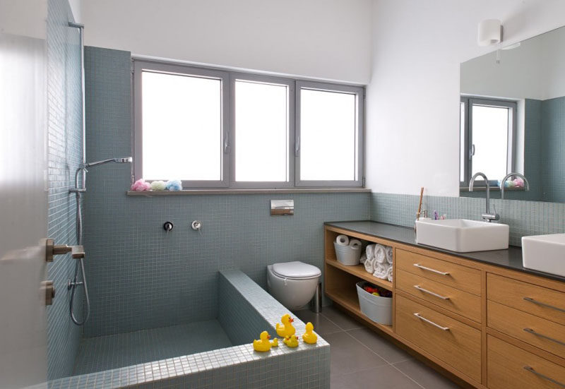 15 Examples of Bathroom Vanities That Have Open Shelving // Having the open shelf next to the bath and toilet provides a place for extra toilet paper and towels, as well as provides a place to store bath toys.