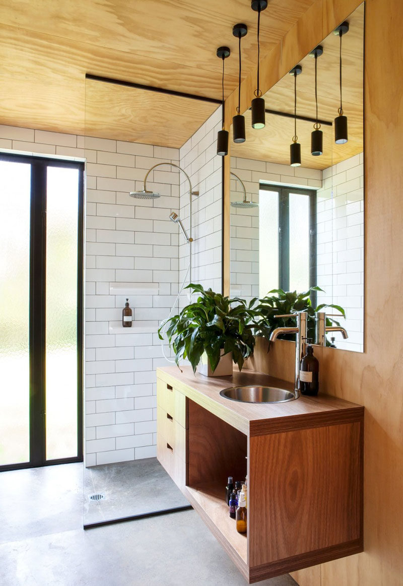 15 Examples of Bathroom Vanities That Have Open Shelving // The vanity in this bathroom contains drawers and a wide open compartment for additional storage.