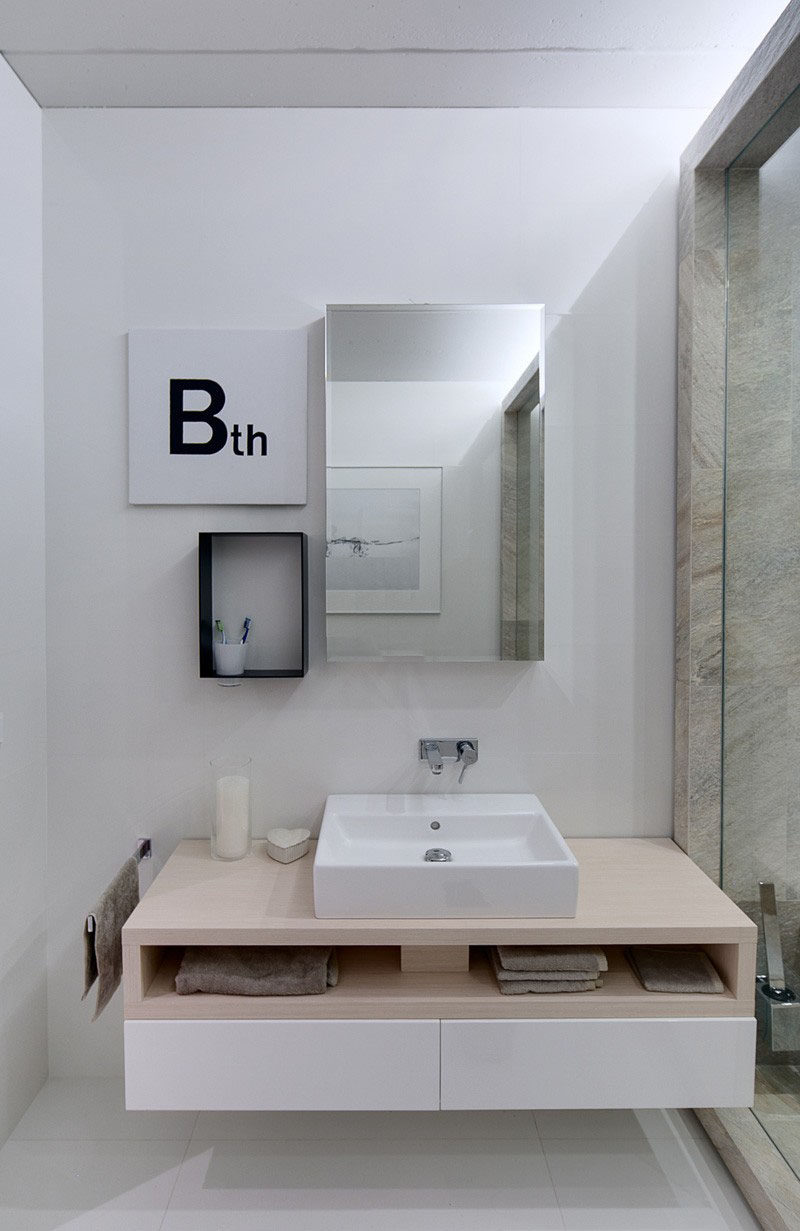 15 Examples of Bathroom Vanities That Have Open Shelving // This modern bathroom has opening shelving to keep each person's towels separate.