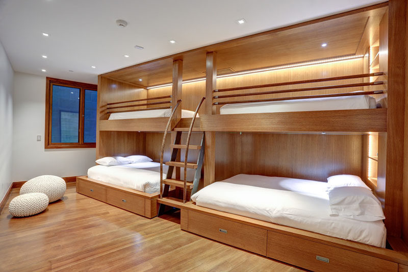 Interior Design Ideas For Sleeping Six People In A Room // Zone 4 Architects designed this wooden bunk bed unit with hidden lighting and storage, that has two larger beds located below the two upper bunks, making it an ideal place to sleep six.