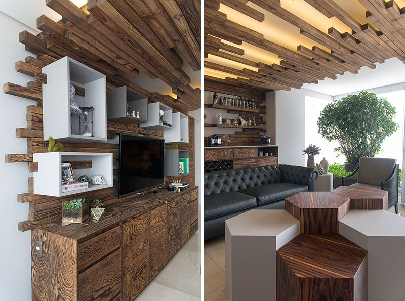 When Kababie Arquitectos were designing this apartment in Mexico City, they decided to define the living room by installing a decorative wooden feature that wraps from one end of the room, onto the ceiling, and then down the wall on the other end.