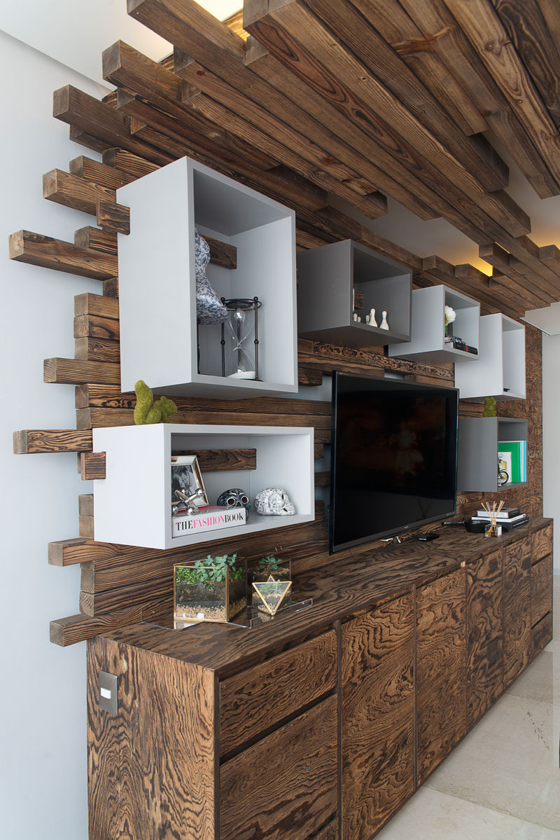 In this living room, there is a wall with a television, cabinetry and box shelving. The box shelving is attached to the wall using wood that matches the ceiling detail.