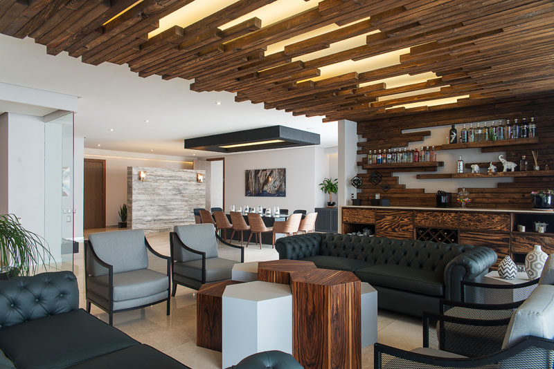 The wooden wall-to-ceiling feature is broken up by sections of soft lighting.