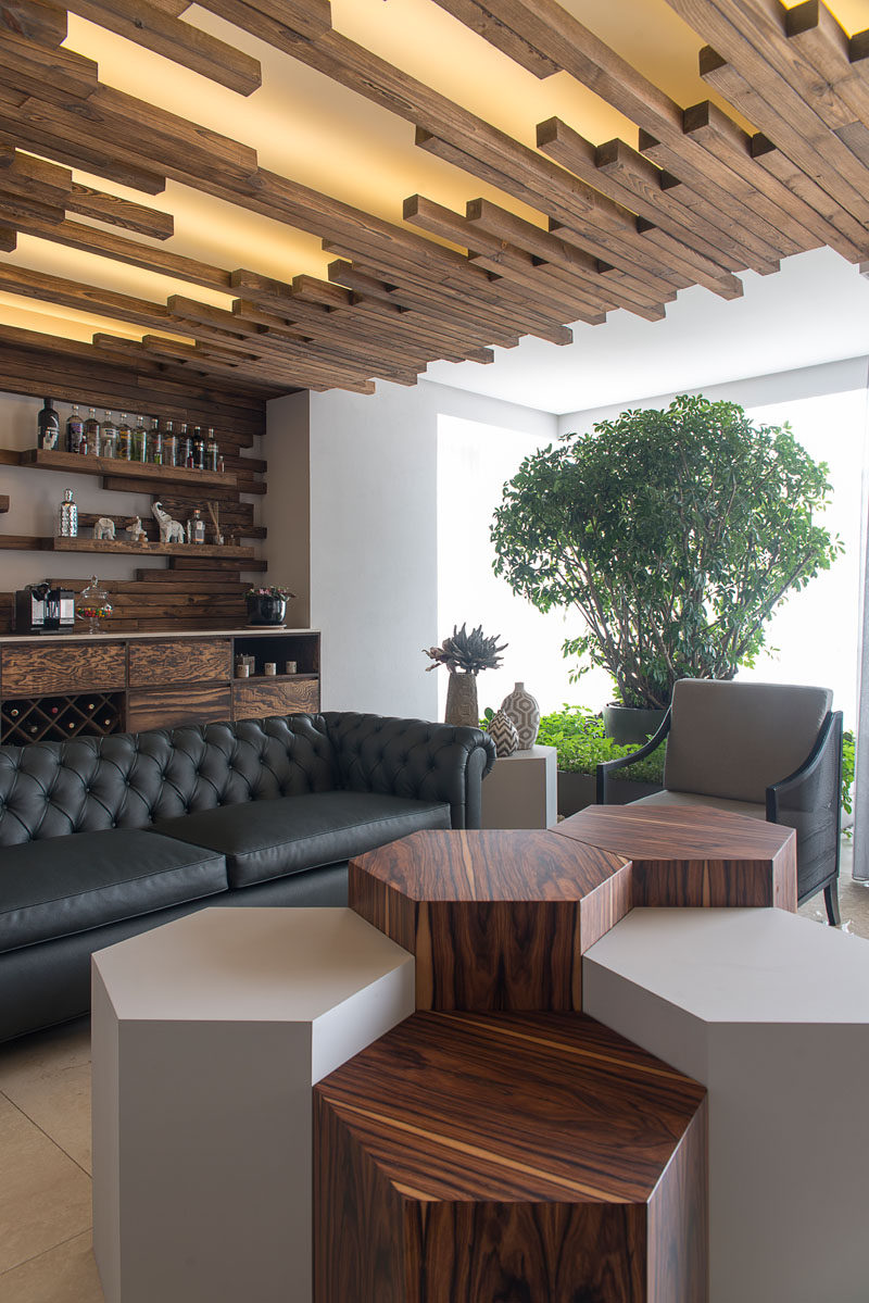 At the end of this living room is a lounge and bar. The floating shelves above the bar blend into the ceiling details, creating a unified and seamless look.