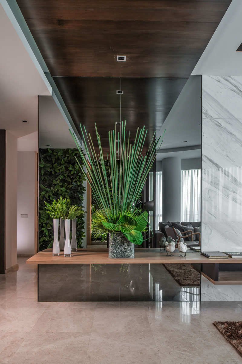 Upon entering this home, there is greenery everywhere, like the green walls and this arrangement positioned in front of a mirror.