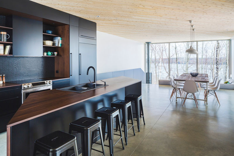 This kitchen has a dramatic color palette of black and deep rich wood.