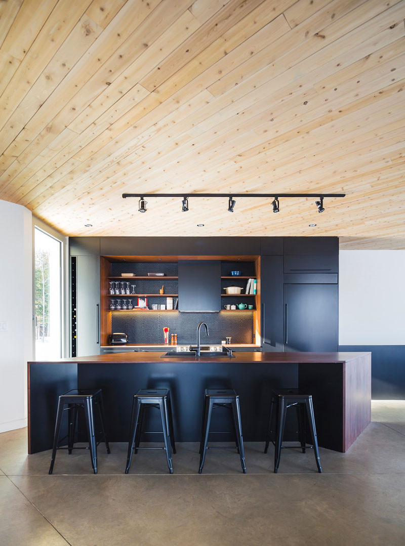 The light cedar wood continues from the outside of the home through to the interior ceiling, and is in direct contrast to the dramatic black and dark wood kitchen.