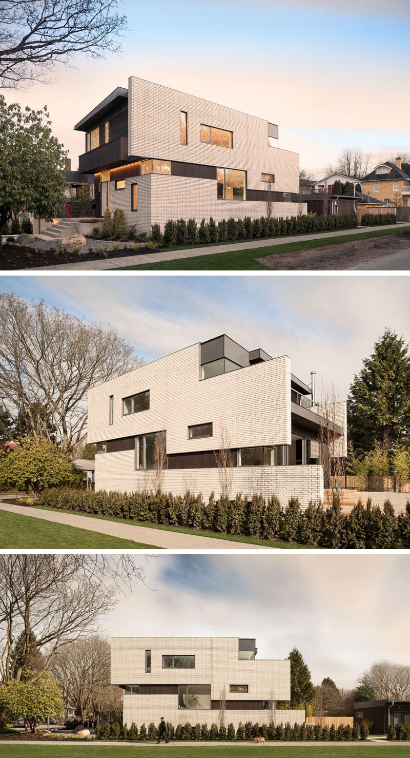 This contemporary home, with a facade of white brick, is located on a corner lot in a quiet neighborhood of Vancouver, Canada. The home, designed by architect Randy Bens, also has dark stained cedar siding running vertically and horizontally, and zinc colored metal trim.