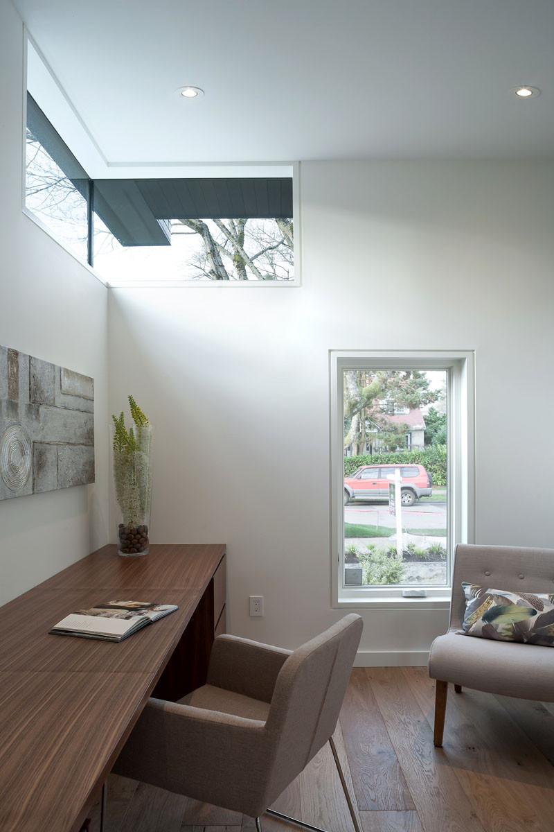 This home office, with wooden walnut desk, has views of the street through a small vertical window.