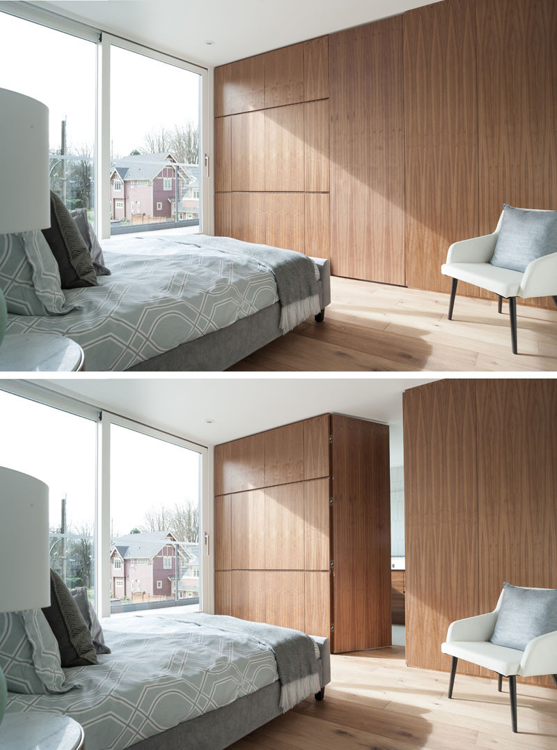 This bedroom features wide plank oak flooring and darker walnut cabinetry. Through a hidden door in the wall of cabinets is an ensuite bathroom.