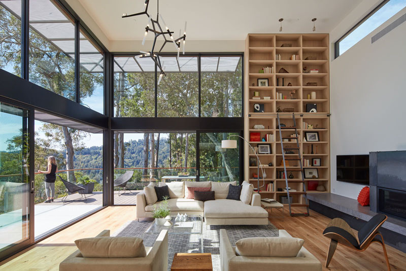 This living room features floor-to-ceiling windows and bookshelf.