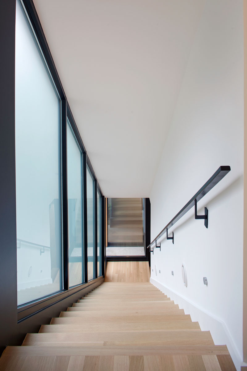 Light wood stairs contrast the black window frames and handrail in this home.