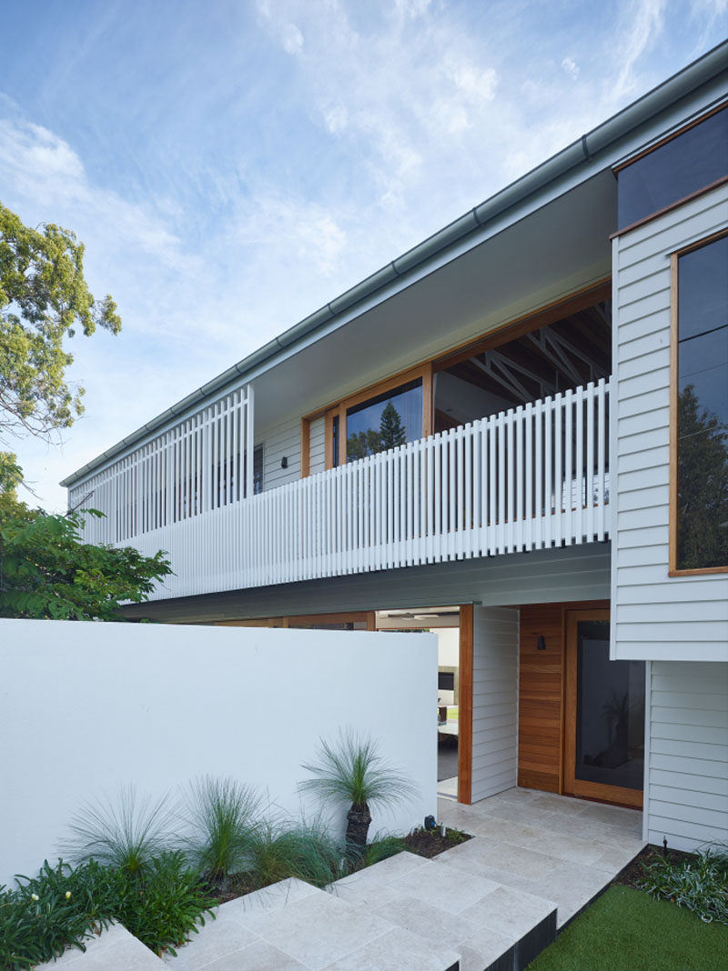 This contemporary home has steps and plants leading you down to the front door.