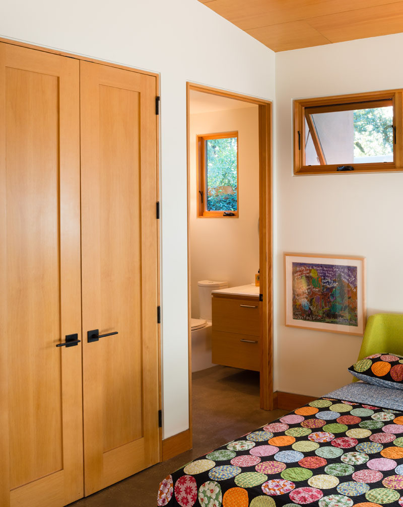 This guest bedroom has an ensuite bathroom and wooden wardrobe for when friends stay over.