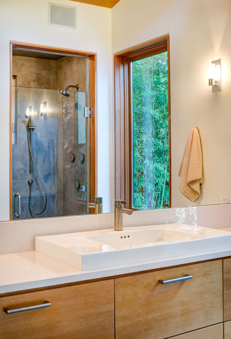 This master bathroom has a wood framed window that matches the frame on the shower door.