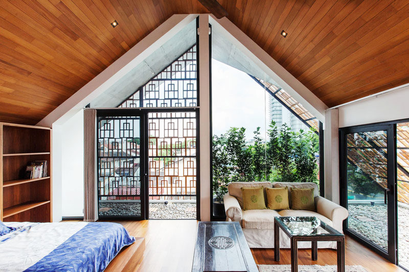 This attic bedroom has a small semi-enclosed balcony and a sitting area.