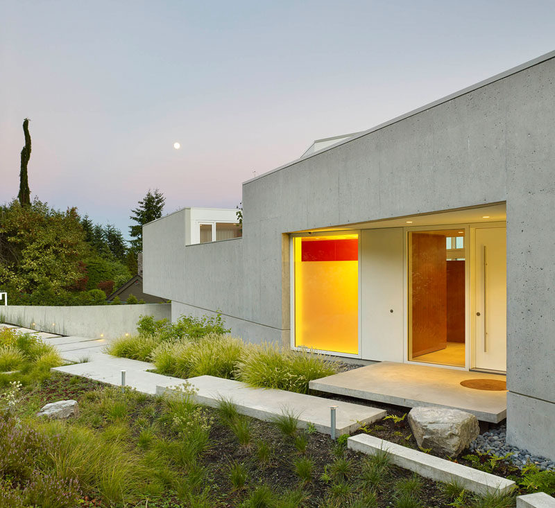 A concrete path surrounded by landscaping, guides you to the front door.