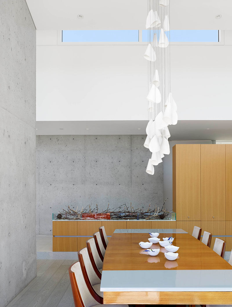 Divided by a concrete wall, the next section is the dining room, that has a sculptural pendant light hanging above the table. Cabinetry adds extra storage space to the area.